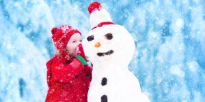 Little girl whispering in the ear of a snowman