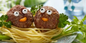 Pair of meatballs decorated to look like characters sitting on top of spaghetti - funny pasta puns concept